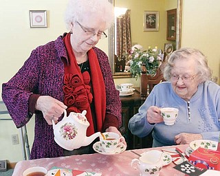 Eunice Hall, left, pours tea as Edith Cardelein looks on during a recent gathering for several women from England. For more than 50 years, a group of English women who all moved to the Youngstown area at least six decades ago often get together and have tea.