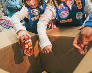 Mia Rucci, 7, left, and Haley Shiley, 7, put cans of food into a box that will be delivered to Second Harvest Food Bank. Their Girl Scout troop teamed up with some respiratory-therapy students at Youngstown State University to collect the food.