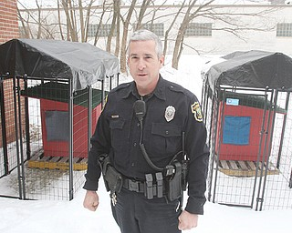 Boardman Police Department officer Jack Neapolitan stands near two new kennels the department will use to temporarily house dogs with no place to go.