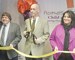 Matt Kresic, chief executive officer of Homes for Kids/Child and Family Solutions, based in Niles, holding scissors, is flanked by agency board members Tom Maley, left, and Tysa Egleton during the ribbon-cutting for the agency's new office on Market Street in Boardman.