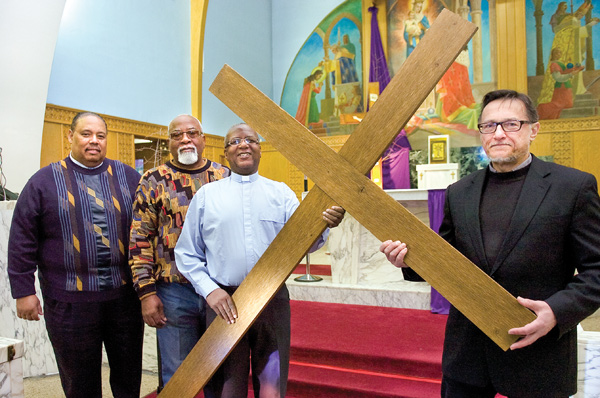 Clergy in Ambassadors for Christ hold a wooden cross that is used in its signature event, a cross walk on Good Friday. From left are the Rev. Jack Pettis, Pastor Roney Tucker, the Rev. George Wilkins and the Rev. Joseph Rudjak.