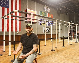 Derrick Dozier, co-owner of Rodeo Music Hall in Austintown, sits in front of what is being called the world's largest beer bong.