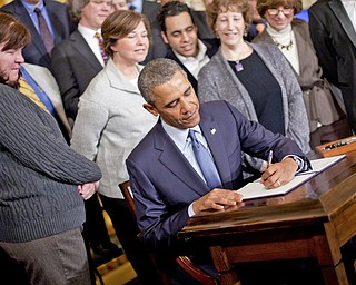 President Barack Obama, surrounded by supporters of the president's memorandum, signs a Presidential Memorandum directing Labor Secretary Tom Perez to modernize overtime protections. Obama signed the memorandum Thursday in the East Room of the White House in Washington.