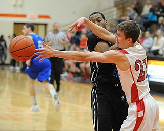 HOWLAND, OHIO - MARCH 25, 2014: Brandon Bates #21 of Badger reaches for the ball after poking it out of the control of Terrell McClain #20 of East during Tuesday nights Frank Bubba Classic boys basketball all-star game at Howland High School.