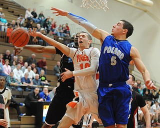 HOWLAND, OHIO - MARCH 25, 2014: Ozzie Hawkins #10 of Newton Falls has the ball blocked by Jake Wolfe #5 of Poland and Terrell McClain #20 of East during Tuesday nights Frank Bubba Classic boys basketball all-star game at Howland High School.