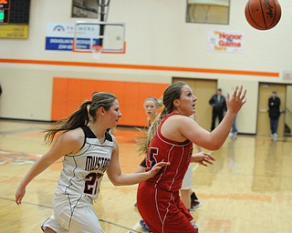 HOWLAND, OHIO - MARCH 25, 2014: Cassie Cluster #15 of Fitch tracks down the loose ball while being pressured by Dayna Ellis #25 of Mathews during the second half of Tuesday nights Frank Bubba Classic girls basketball all-star game at Howland High School. Mahoning County won  67-62.