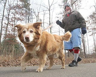 Jerry Schromofsky and his dog, Missy, walk in Mill Creek Park on Tuesday. Schromofsky, who lives in Youngstown, said he walks for exercise several days a week and also regularly works out at a gym.