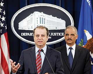 Attorney General Eric Holder listens at right as U.S. Attorney for the Southern District Preet Bharara talks about the $1.2 billion settlement with Toyota over its disclosure of safety problems during a news conference at the Justice Department in Washington.