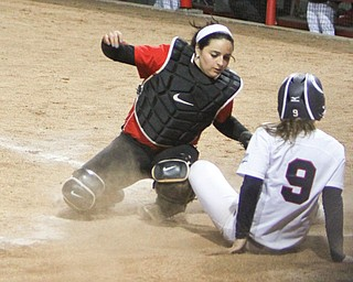 Robert Morris's Tess Apke kicks up dust as she tries to avoid the tag by Youngstown State catcher Maria Lacatena as she slides into home during the second game of their doubleheader Wednesday at the YSU softball complex. The Penguins lost both games to the Colonials, 6-1 and 6-4.