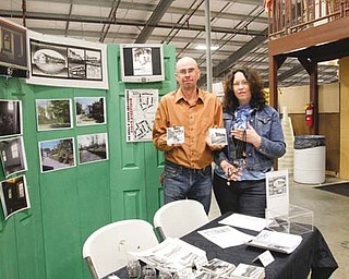 Tim Sokoloff and Linda Gens hold up handmade coasters and necklaces they have for sale at Four Seasons Flea and Farm Market in Youngstown. Sokoloff and Gens are the president and executive director, respectively, of the Iron Soup Historical Preservation Co. They will be selling the items throughout April to bring more former Youngstown Sheet & Tube Co. worker housing units in Campbell out of blight and into tenancy.
