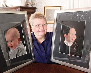 Patty McCauley Guarnieri of Boardman poses with photographs of her grandsons, 10-month-old Cole Muir and 6-year-old Luke Lantz. Guarnieri has been battling advanced kidney cancer for almost 24 years.