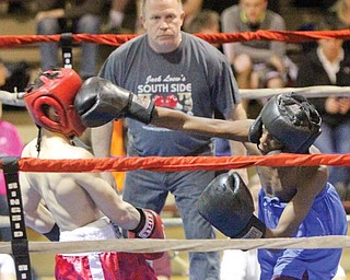 Referee Jack Loew watches as Re'yan Hammonds of Farrell, right, lands a right to the jaw of Youngstown Christian's Emanuel Padilla in their bantamweight bout Thursday during Round 2 of the K.O. Drugs High School Boxing Tournament at the North Lima Business Complex. Hammonds won by unanimous decision to advance to the final next week against his cousin Portez Smith.