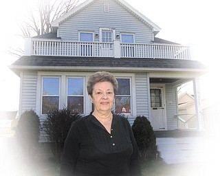 Lena Pilgrim stands in front of her home at 675 Perkinswood Blvd. SE, Warren, which is where rock drummer Dave Grohl and his family lived in 1969, when Grohl was born.