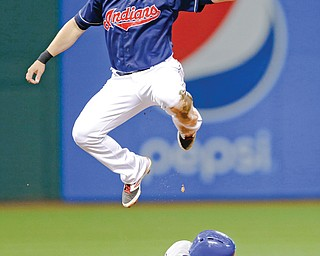 Indians shortstop Asdrubal Cabrera leaps over the Royals' Alcides Escobar (2), who stole second base in the fourth inning of a game Tuesday night at Progressive Field in Cleveland. Escobar went to third as the high throw went into center field.
