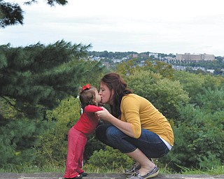 """Keith Edenfield sent this photo of his wife, Michelle, and daughter Klara, 19 months, on the wall inside Fellows Riverside Gardens overlooking Youngstown. """"Our daughter was just learning how to give hugs and kisses and asked to """"kiss Mommy"""" as my wife was standing with her on the wall. Needless to say, this is the best picture I have ever taken."""""""