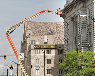 A highlift is used to inspect, measure and photograph the roof overhang on the Front Street side of the courthouse in preparation for the $6 million restoration of the historic building that will begin this summer.