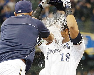 The Brewers' Khris Davis is doused after getting the game-winning hit — a walk-off two-run single — during the ninth inning of Thursday's baseball game against the Pittsburgh Pirates in Milwaukee. The Brewers won 4-3.