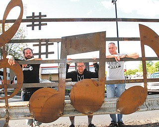 Warren artist Aaron Chine, left, poses with some of the 12 metal musical notes that were welded at the David Grohl Alley in Warren. With Chine are Joe O'Grady, center, who came up with the idea, and Tim Drummond, who helped with the project.