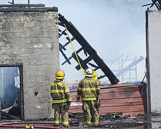 Struthers firefighters Mike Donofrio, left, Brian Hallquist and Walter Baber, in front of Hallquist, tear down a portion of the building that, before Monday's destructive fire, housed Struthers Chair and Tent Rental. The cause of the fire has not been determined.