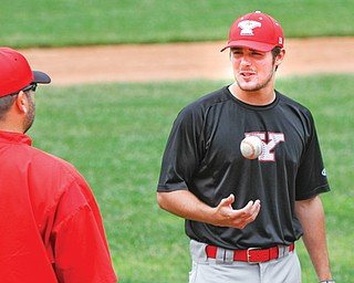 Youngstown State junior pitcher Ryan Krokos, right, talks with Penguins assistant coach Jason Neal during practice Tuesday at Eastwood Field. YSU, fresh off a stunning Horizon League tournament run, is preparing for an NCAA regional appearance beginning Friday night in Bloomington, Ind.