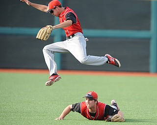 BLOOMINGTON, INDIANA - MAY 30, 2014: Outfielders Jonas Wellan #12 jumps while trying to play the ball and avoid a sliding Kevin Hix #1 of Youngstown State after a bloop Indiana hit during Friday nights regional tournament game against Indiana University. (Photo by David Dermer/Youngstown Vindicator)
