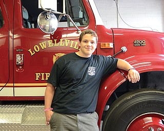 Christopher Inskeep, 17, stands beside a firetruck at the Lowellville Fire Department's Station 31 on McGaffney Street. The Lowellville High School senior hopes to become one of the first participants in the department's new cadet program.