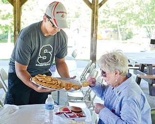 Austin Yemma, a senior at Struthers High, serves cookies to Marinell Szalaj of Struthers during the event. Yemma and other members of the school's boys basketball team were among those who volunteered to help out at the event.