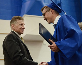 Katie Rickman | The Vindicator .Jackson Milton's Tyler Staton walks across the platform and receives his diploma from Board of Education Vice President Victor Wolfe June 6, 2014.