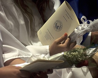 Kelli Cardinal/The Vindicator.A graduate holds her program and a single red rose Sunday before walking into the fieldhouse for commencement at Poland Seminary High School.