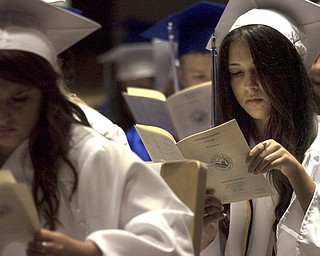 Kelli Cardinal/The Vindicator.Graduate Alexa Ciccone flips through a program Sunday before walking into the fieldhouse for commencement at Poland Seminary High School.