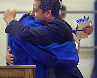 Kelli Cardinal/The Vindicator.Commencement speaker Michael Masucci hugs graduate and class president Alex Ankerman after Ankerman presented him with a gift Sunday from the senior class during the ceremony at Poland Seminary High School.