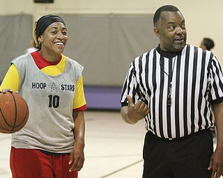 Essence Bell of Akron confers with Northeast Ohio Adult Women's Basketball League director Delmas Stubs during one of Sunday's games at the McGuffey Center in Youngstown.