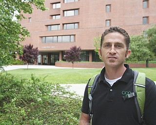 Campus minister Garret White walks on the YSU campus, where the Coalition for Christian Outreach and