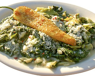 Fried Italian Greens appetizer topped with pecorino Romano cheese and a Hungarian hot pepper.