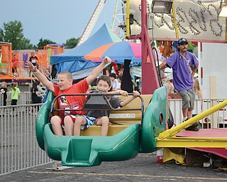 At left, Mark Cole throws his hands in the air, as Cody Rivera attempts to defy gravity while on a ride at the 41st annual St. Nicholas Church Festival on Wednesday evening. The two 10-year-olds, both of Youngstown, were among those who came out for the festival's opening day, despite the threat of rain.