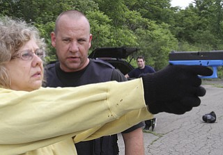 William D Lewis the vindicator  Hubbard PD sgt Chris Moffitt gives advice and training to Vindy reporter Jeane Starmack during a training exercise 6-12 at a vacant building in Hubbard.