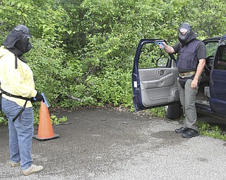 William D Lewis the vindicator  Hubbard PD sgt Chris Moffitt , right, portraying bad guy, and Vindy reporter Jeane Starmack during a training exercise 6-12 at a vacant building in Hubbard.