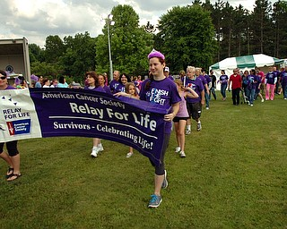 Kelli Cardinal/The Vindicator.Nicole Novotny, center, 23, of Youngstown, leads the survivor lap Friday during the 2014 Austintown Relay For Life event in Austintown Township Park.  Novotny was diagnosed with Non Hodgkin's Lymphoma at age 19.
