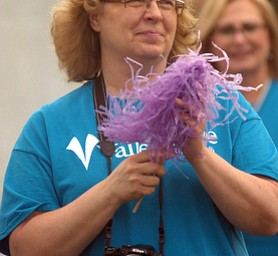 Kelli Cardinal/The Vindicator.Deb Bishop, of Austintown, shakes a pompom Friday for those walking the survivor lap during the 2014 Austintown Relay For Life event in Austintown Township Park.
