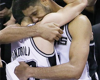 San Antonio Spurs guard Manu Ginobili, left, and forward Tim Duncan embrace in the final moments of Game