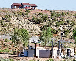 In this June 9 photo, an oil-and-gas well pad and storage tanks sit below a home in a sparsely populated area near New Castle, Colo., a small farming and ranching settlement on the Western Slope of the Rockies. Four in 10 new oil and gas wells near national forests and fragile watersheds or otherwise identified as higher pollution