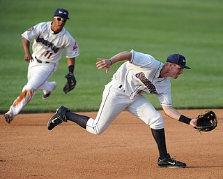 NILES, OHIO - JUNE 17, 2014: Infielder Austin Fisher #12 of the Scrappers charges in to make a play on a ground ball in the top of the 4th inning during Tuesday nights New York Penn League game at Eastwood Field. (Photo by David Dermer/Youngstown Vindicator) Infielder Ordomar Valdez #11 pictured.