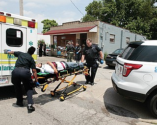 The owner of a South Avenue store is wheeled into an ambulance Wednesday after he and a 10-year-old boy inside the store were wounded by two men inside who were shooting at each other. His name was not available at press time. Police are still searching for the two gunmen.