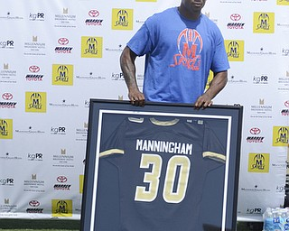Kate Rickman | The Vindicator.Mario Manningham stands behind his high school jersey during the a short ceremony where Coach Steven Arnold declared #30 a retired number for Warren G. Harding High School football June 21, 2014.