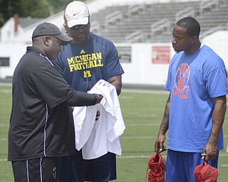 Katie Rickman | The Vindicator.Coaches Alan Caldwell (left) and Dave Arnold speak with Mario Manningham on the field at Warren G. Harding High School June 21, 2014.