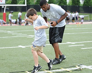 YOUNGSTOWN, OHIO - JUNE 21, 2014: Isaac Strock works on quick feet in a rope drill with Brad Smith next to him encouraging him during the Brad Smith Football Camp at Stambaugh Stadium on the campus of Youngstown State Saturday morning. (Photo by David Dermer/Youngstown Vindicator)