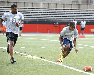 YOUNGSTOWN, OHIO - JUNE 21, 2014: Tristan Ballard prepares to scoop up the football to score with Brad Smith next to him encouraging him during the Brad Smith Football Camp at Stambaugh Stadium on the campus of Youngstown State Saturday morning. (Photo by David Dermer/Youngstown Vindicator)