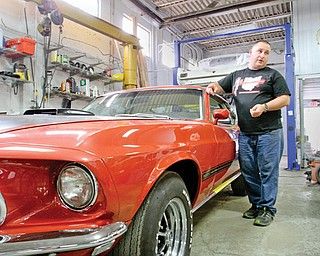 Nate Miller stands near a 1969 Mustang Mach 1 that his Canfield company is restoring. Miller owns Buckeye Classic Car Restoration. He's also branching out into reproducing Mustang Fastbacks through a sister company called Thoroughbred International.