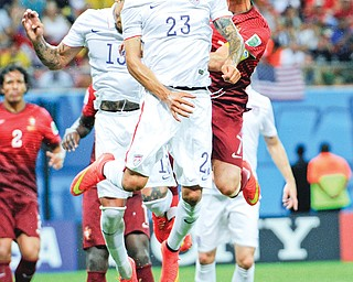 The United States' Fabian Johnson (23) heads the ball away from Portugal's Cristiano Ronaldo, right, during the
