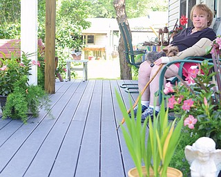 Linda Clark of Hubbard and her dog, Harry, enjoy their new deck, built by the Home Builders & Remodelers Association of the Valley as part of its 2014 community service project. Clark continues to recover from a November 2013 stabbing she suffered when a man attacked her at Sharon Regional Health System.